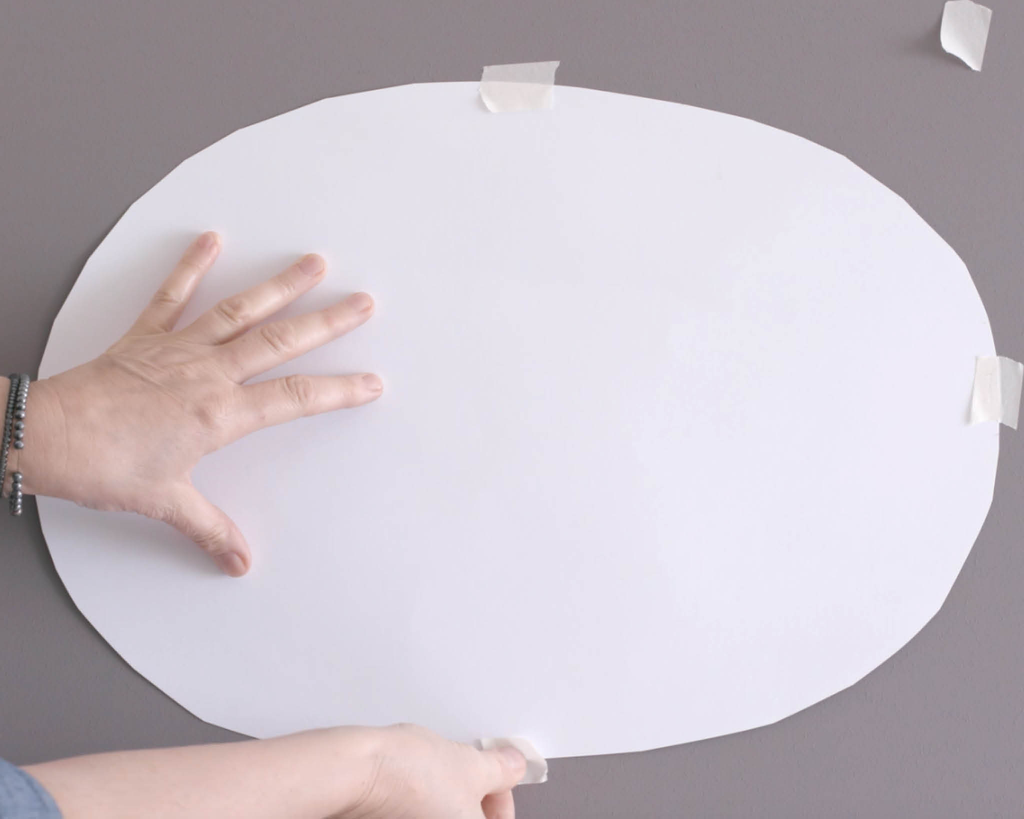 Tape your oval to the area you'd like to paint