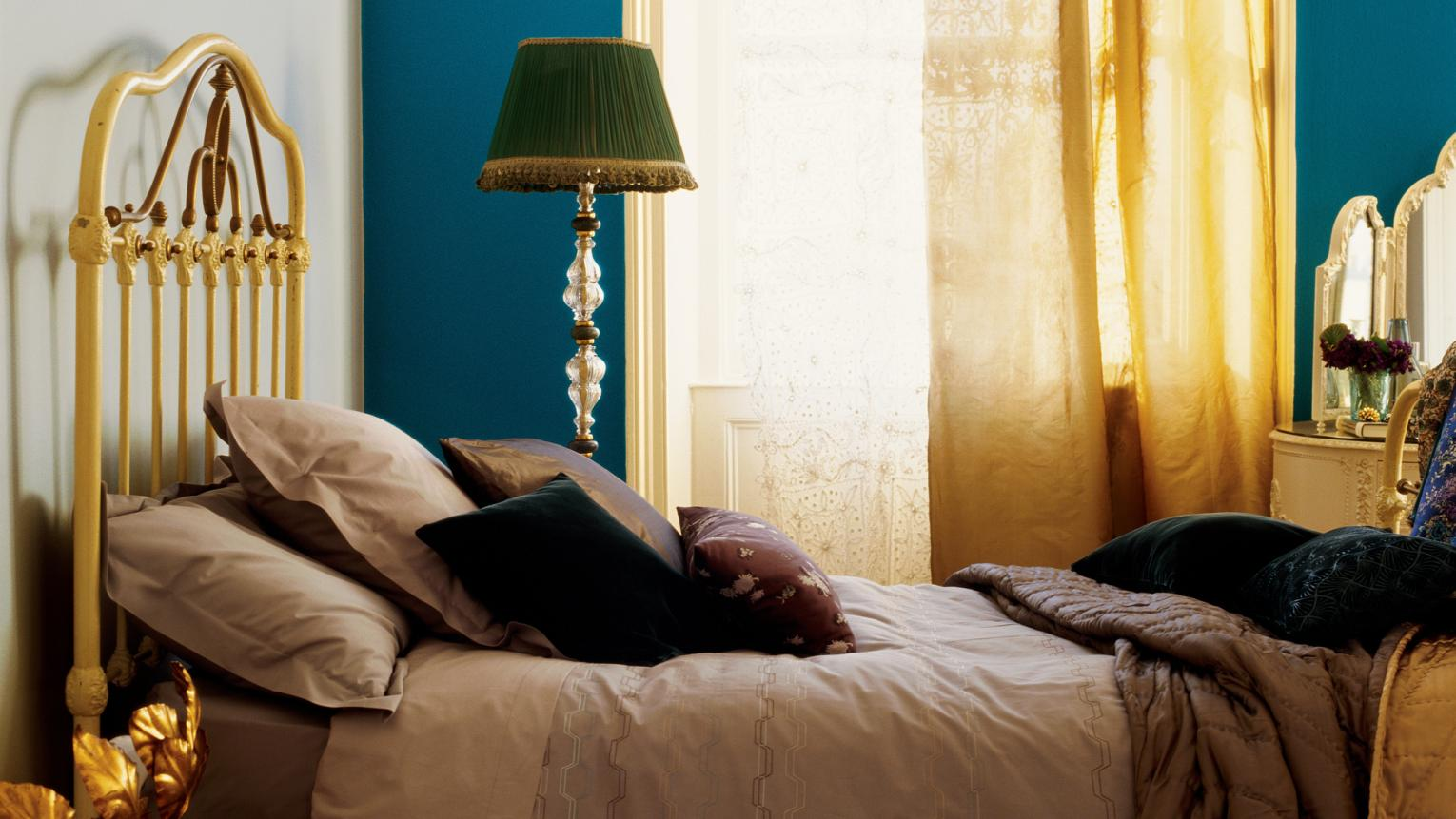 A bold wall of warm teal adds depth to an elegant bedroom.