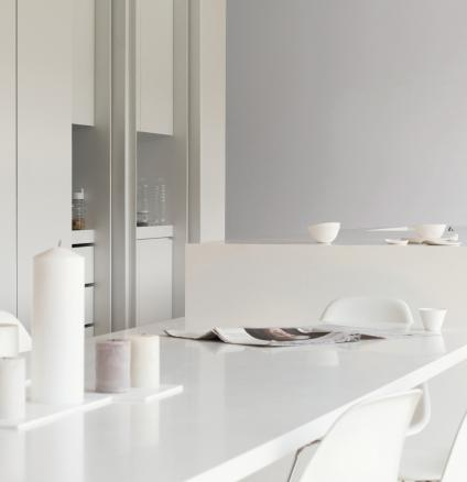 Add warmth to a minimalist white kitchen with accents of pale silvery grey.