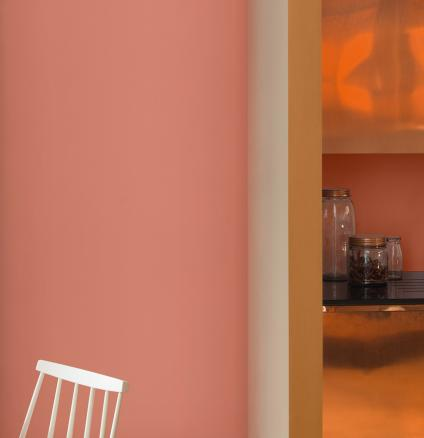 For a kitchen colour scheme guaranteed to wow your guests, pair copper orange paint with copper cabinetry.