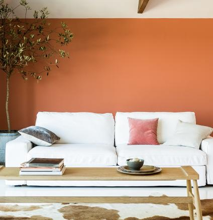 Create a relaxing living room by pairing warm hues, like copper orange, with soft neutrals and natural materials.